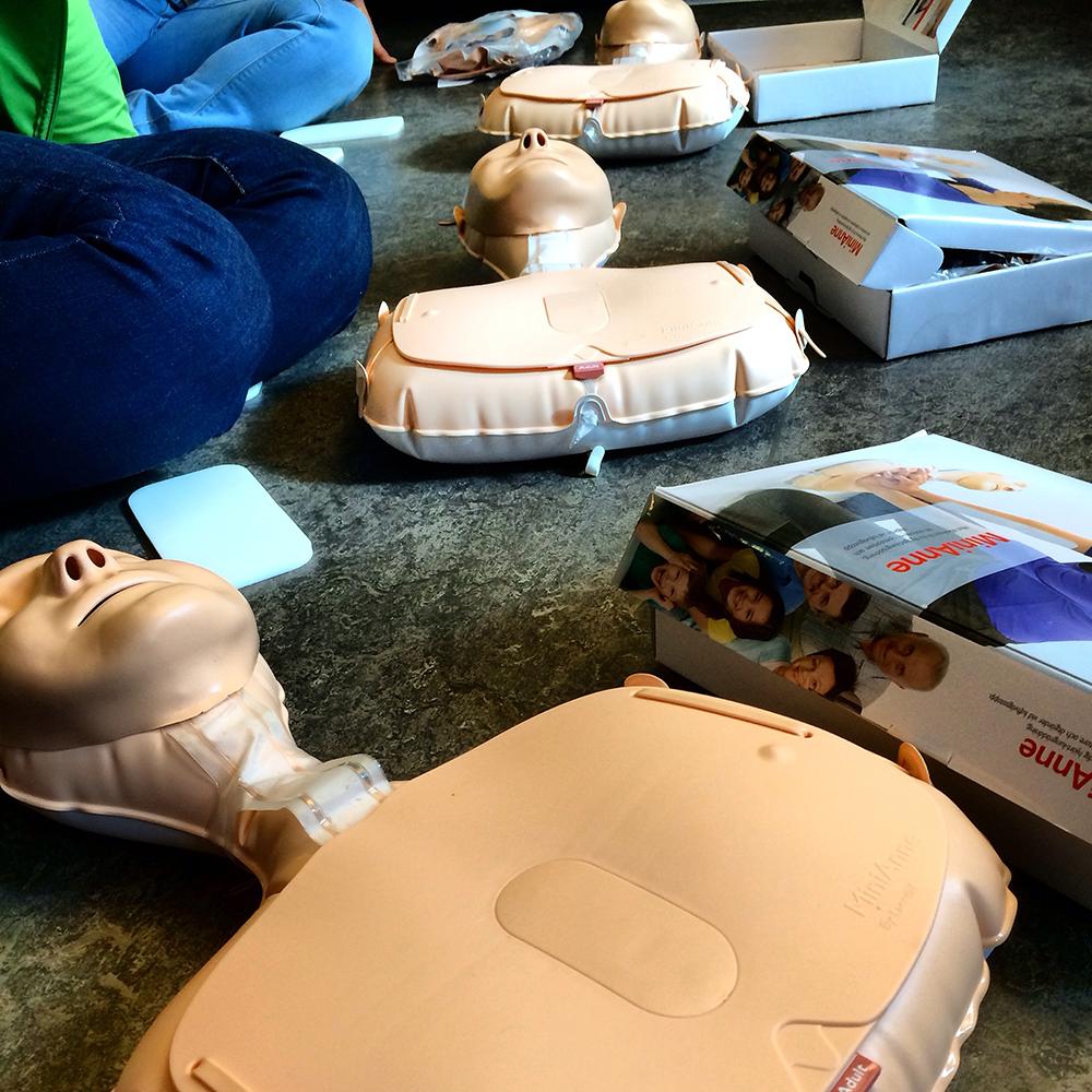 Med hjälp av MiniAnne-dockan övar vi oss på att göra först 30 hjärtkompressioner och sedan två inblåsningar.